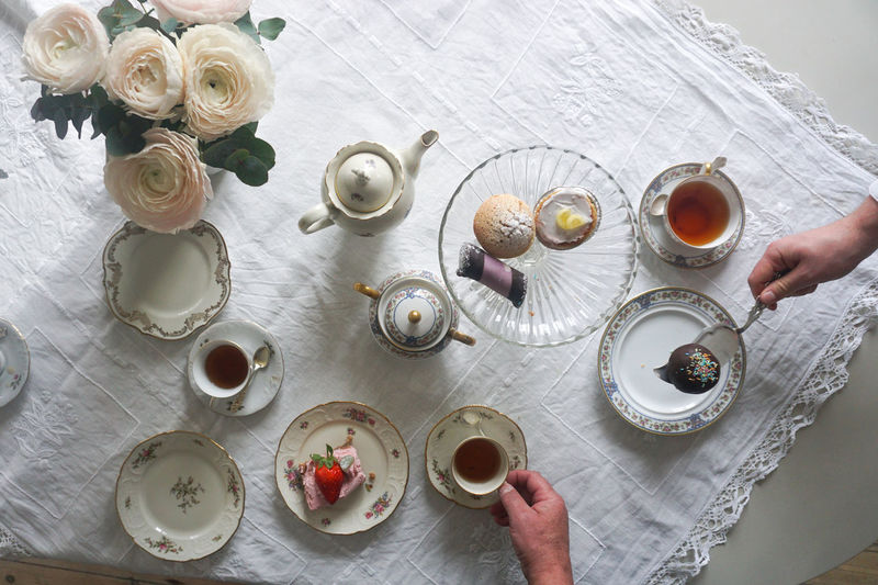 tea party Directly Above Cake Cakes Sweet Food Indulgence Temptation Human Body Part Human Hand Eating Tea Tea - Hot Drink Tea Cup Human Hand Table High Angle View Close-up Pastry Served Tablecloth Setting The Table Empty Plate Place Setting Centerpiece Plate Serving Size