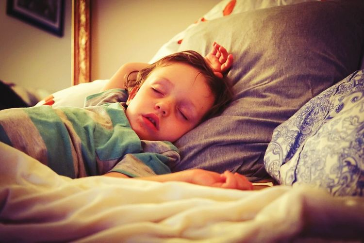 Close-up of cute boy sleeping on bed at home