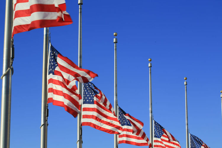 Low angle view of american flags against clear blue sky