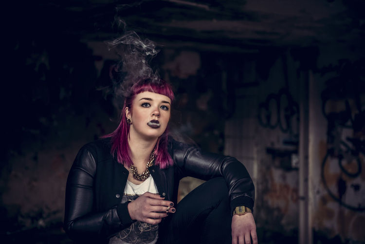 Portrait Of Young Woman Smoking Cigarette While Sitting In Abandoned Building