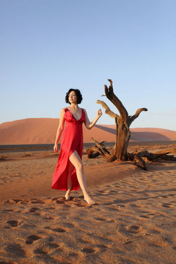 Portrait of young woman standing on sand dune in desert against clear sky