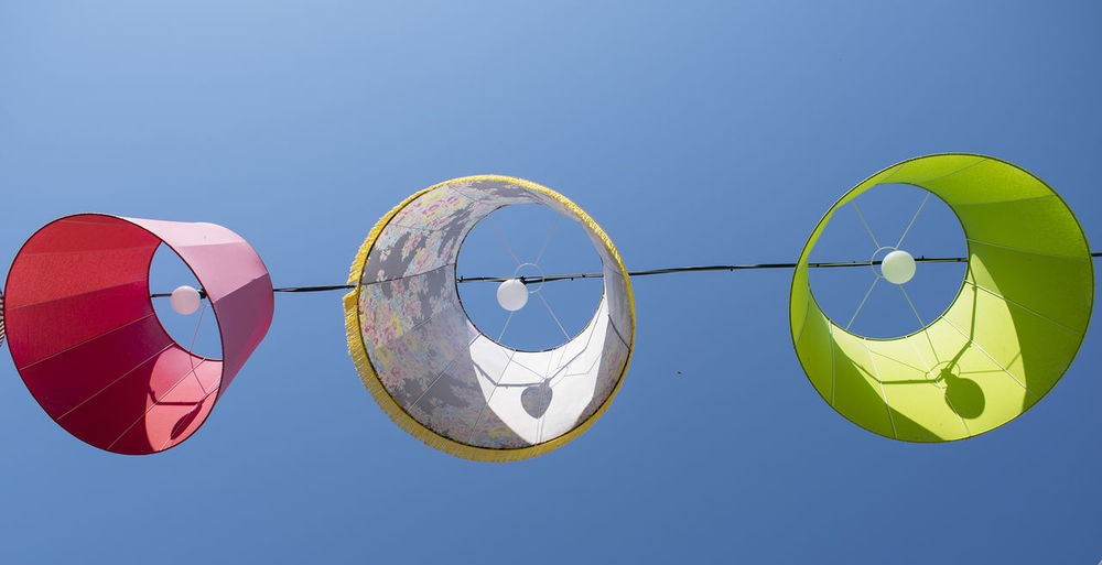 Low angle view hanging lamps against clear blue sky