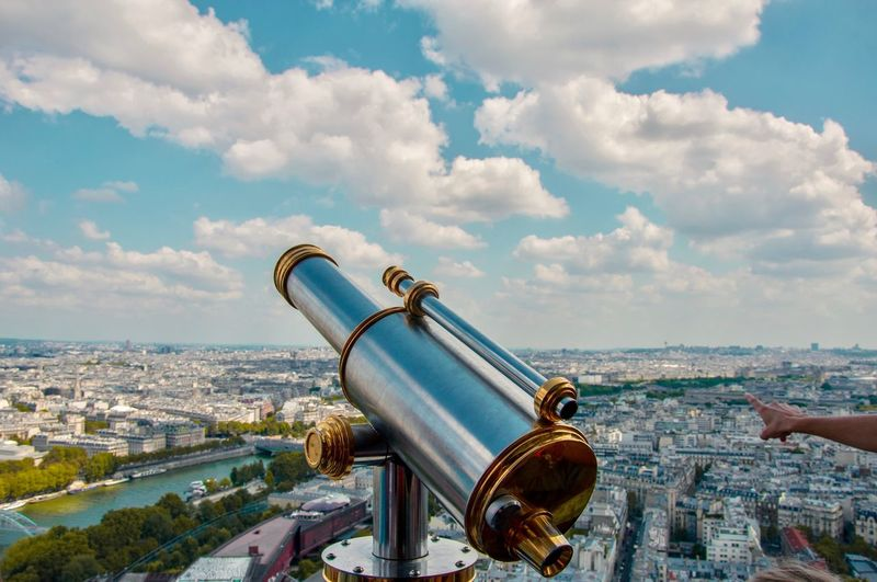 Close-up of telescope against cityscape and sky
