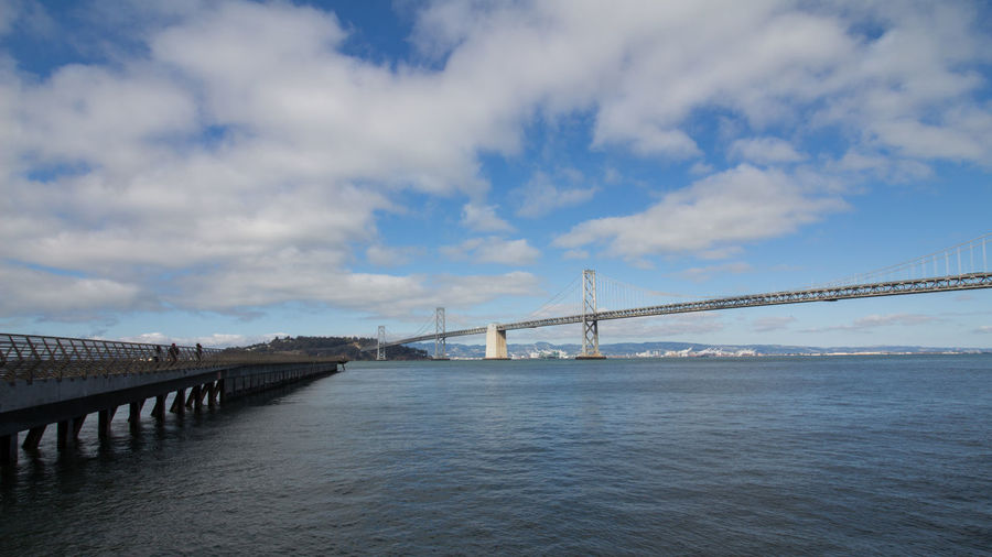 Bridge over calm sea against cloudy sky