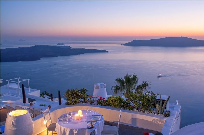 Illuminated Candles On Table At Restaurant In Santorini Against Sky During Sunset