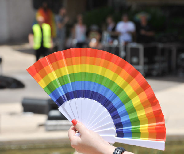 Cropped hand of woman holding colorful folding fan