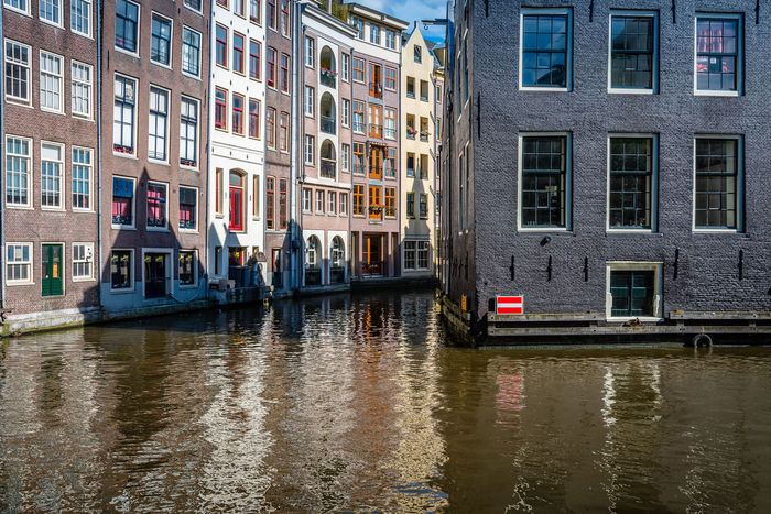 Amsterdam cityscape with canals in Red Light District Amsterdam Architecture Bridge - Man Made Structure Building Exterior Canal City Cultures Day Gondolier No People Outdoors Red Light Red Light District Tourism Tranquil Scene Transportation Travel Travel Travel Destinations Vacations Water Working