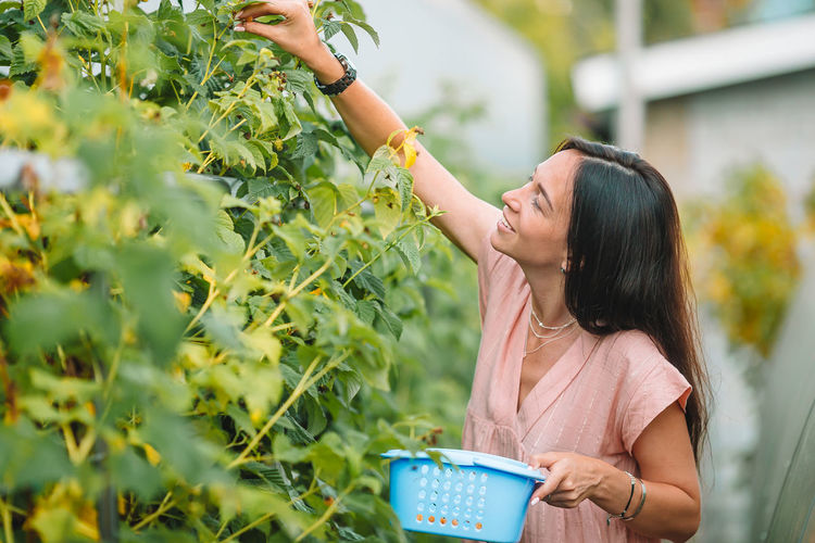Woman holding ice cream cone against plants