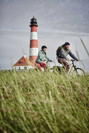 People on field by lighthouse against sky