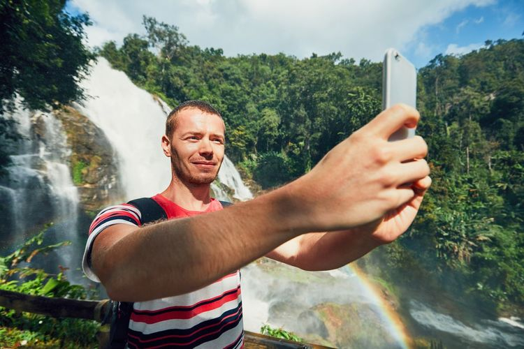 Young tourist taking a selfie against Wachirathan waterfall. Chiang Mai Province, Thailand. Exploring Fun Nature Travel Communication Connection Enjoyment Jungle Lifestyles Mobile Phone Nature One Person Outdoors Photo Messaging Photographing Photography Themes Rainforest Selfie Smart Phone Smiling Using Phone Vacation Waterfall Wireless Technology Young Adult