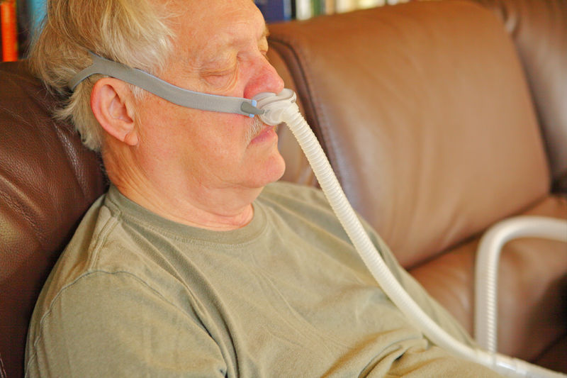 Older man with CPAP breathing assistance Senior Adult Indoors  One Person Sitting Sofa Close-up Casual Clothing Relaxation CPAP Machine Tubing Breathing Treatment Sleep Apnea Condition Medical Healthcare Patient Man Continuous Airway Continous Positive Airway Pressure Sleeping Napping At Home Attachment Device
