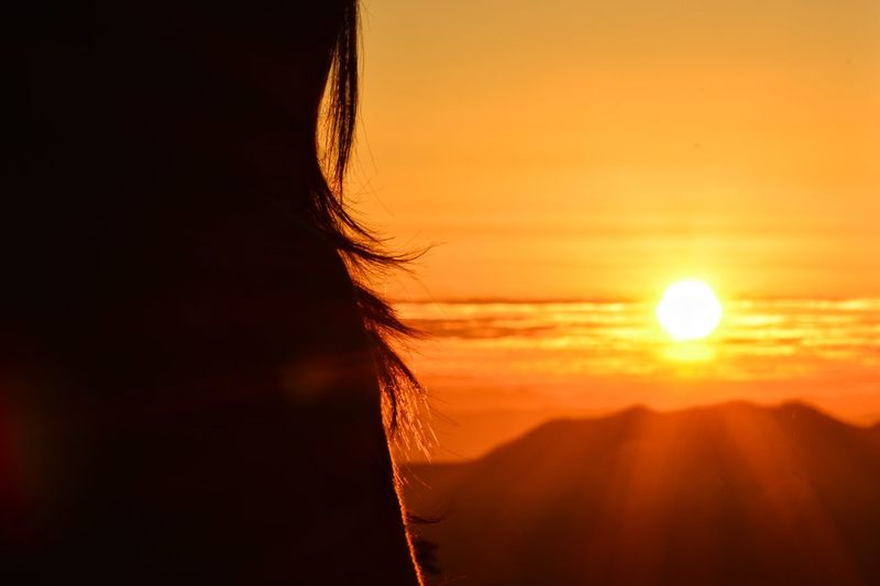 Close-up of woman against orange sky during sunset