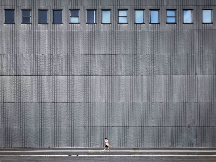 Side view of man walking against modern building
