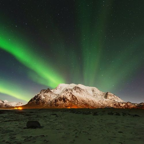 Scenic view of northern lights over mountain