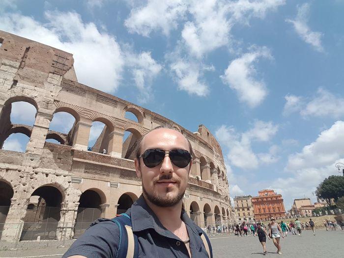 Portrait of man wearing sunglasses against coliseum
