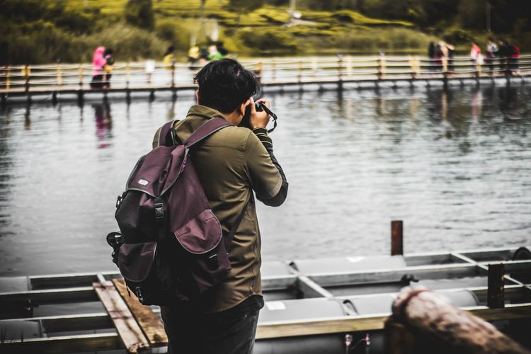 Rear view of man photographing at riverbank