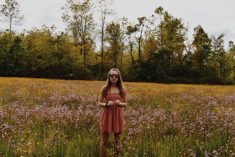 Young Woman Wearing Sunglasses Standing On Grassy Field