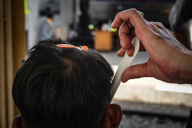 Cropped hand of barber combing male customer hair