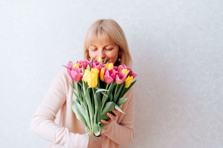 Midsection of woman holding pink tulips against white wall