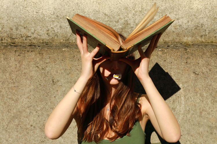Midsection of woman reading book against wall