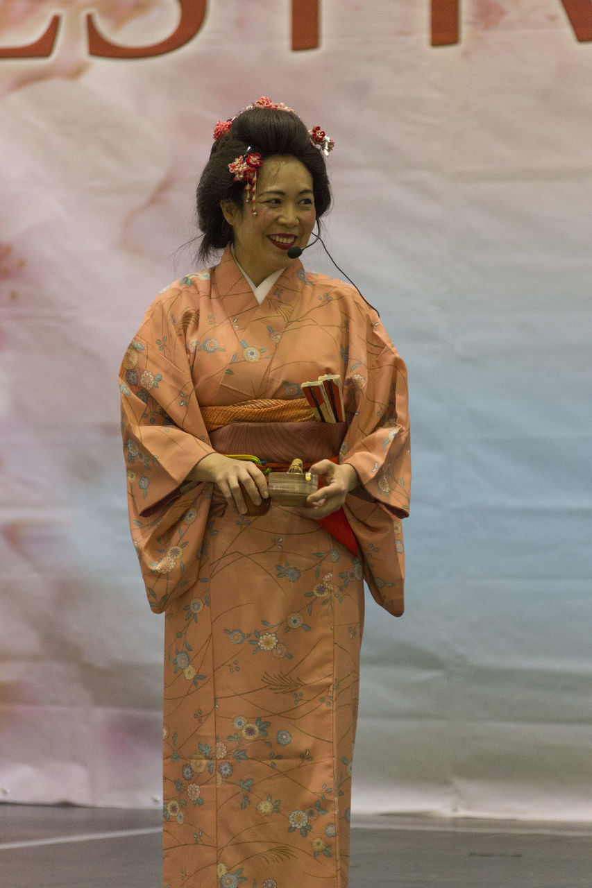 traditional clothing, real people, one person, kimono, women, standing, cultures, lifestyles, young adult, day, young women, sari, outdoors, smiling, adult, people