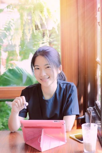 Girl using tablet to do business. Sitting Smiling Lifestyles Table Happiness Indoors  Enjoyment Real People Young Women Cafe Business Modern Daylight Leisure Activity Tablet Computer Asian  Pretty Girl Portrait Relaxing Window Fashion Wireless Technology Connection Communication Social Network The Week On EyeEm
