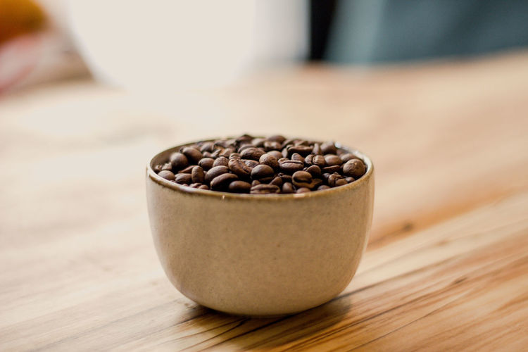 Food And Drink Food Freshness Close-up Table Indoors  Focus On Foreground Brown Wood - Material Coffee Coffee - Drink Still Life Roasted Coffee Bean No People Selective Focus Seed Wellbeing Container Raw Food Bean Caffeine