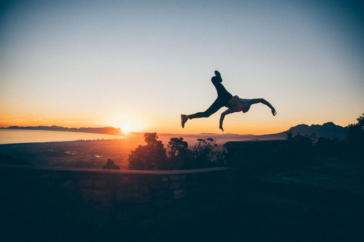 Man jumping from retaining wall against sky during sunset