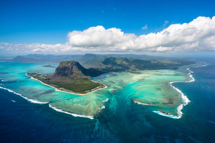 An aerial view of the Underwater Waterfall and Le Morne in Mauritius Aerial View Africa Beach Beauty In Nature Blue Cloud - Sky Day Horizon Over Water Le Morne-Mauritius Mauritius Mountain Nature No People Outdoors Scenics Sea Sky Tranquil Scene Tranquility Travel Destinations Underwater Waterfall Water Waterfront