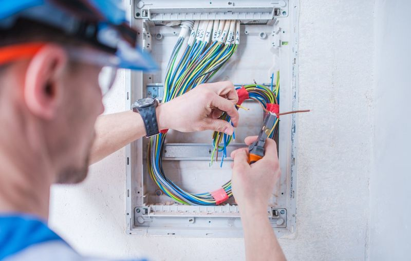 Close-Up Of Man Cutting Cables Against Wall