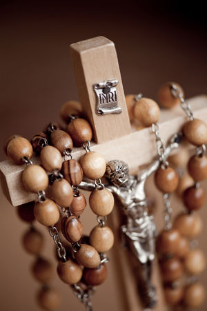Figurine of Jesus Christ in wooden rosary made of beads dangle on wooden cross, INRI sign above, vertical orientation, nobody. Bead Bead-roll Beads Belief Believe Catholic Catholicism Close-up Closeup Cross Crucifix Devotional Effigy Faith God INRI Jesus No People Religion Religious  Rosary Wooden