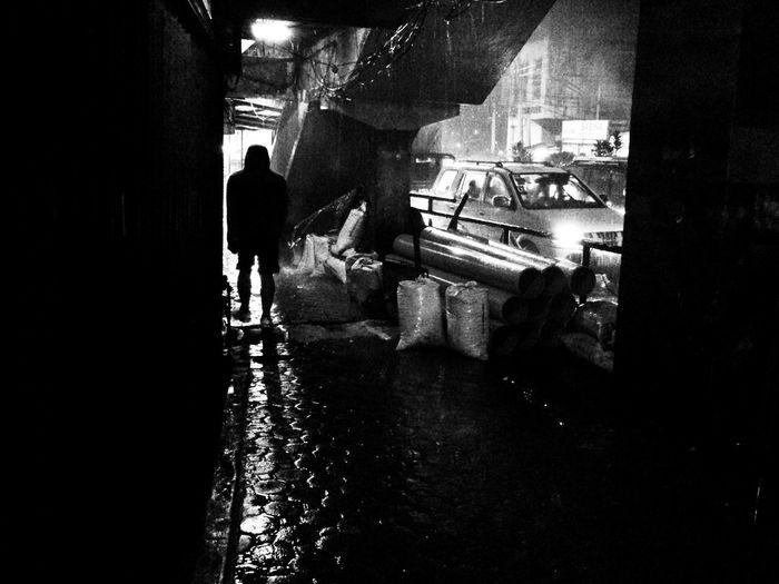 Rear view of silhouette man walking on street in city