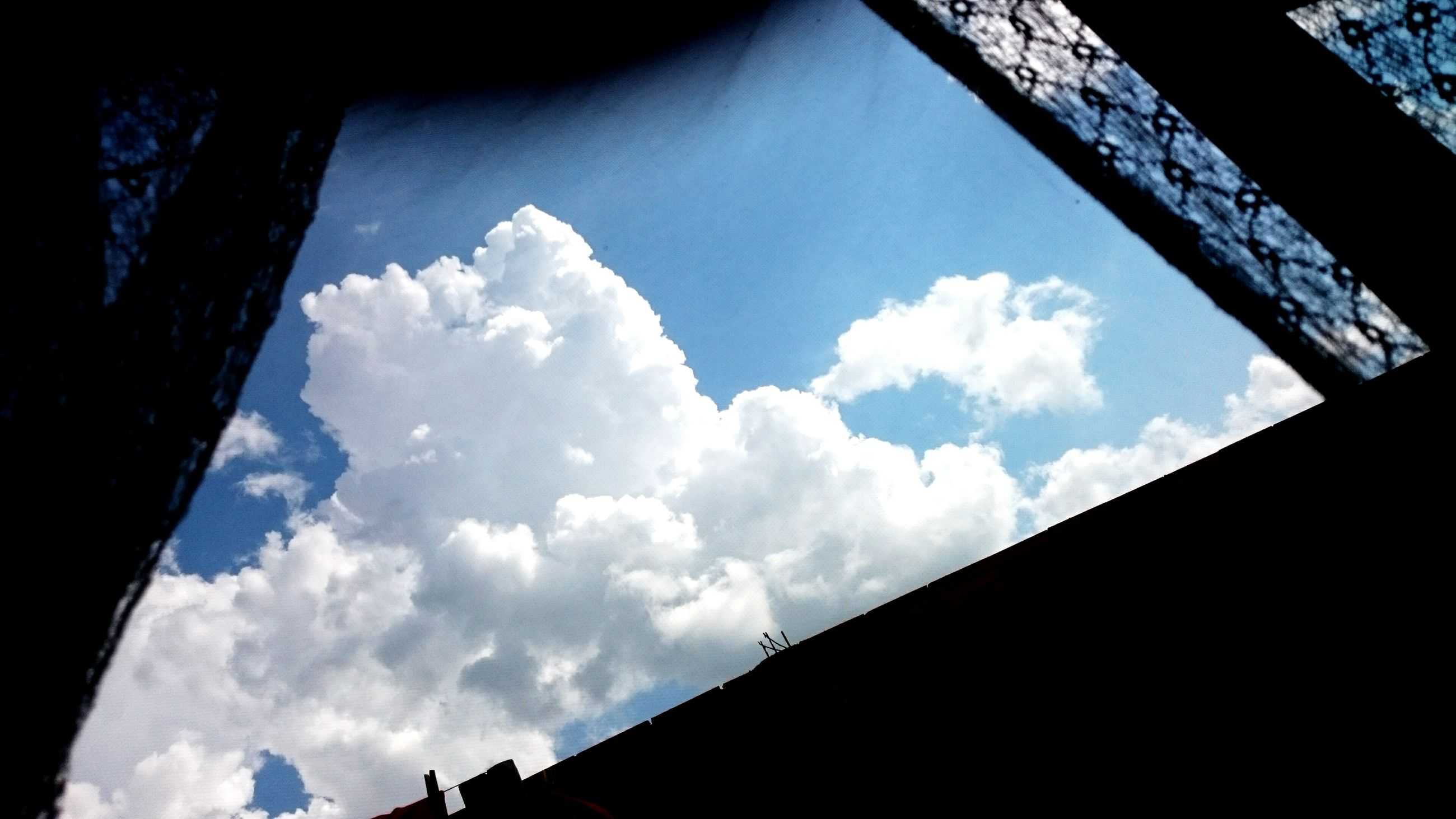 low angle view, sky, architecture, built structure, cloud - sky, building exterior, cloud, building, directly below, cloudy, day, window, no people, glass - material, outdoors, sunlight, silhouette, city, high section