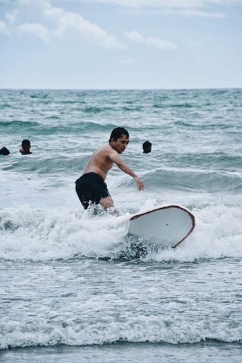 Shirtless man surfing in sea against sky