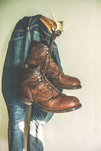 Leather shoes and jeans hanging on the wall Vintage One Person Shoe Real People Indoors  Body Part Casual Clothing Human Body Part Leather Jeans Men Lifestyles Clothing Denim Boot Sunlight Low Section Human Leg Adult