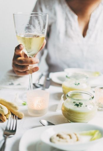 Cropped image of woman holding wineglass with vichyssoise on table