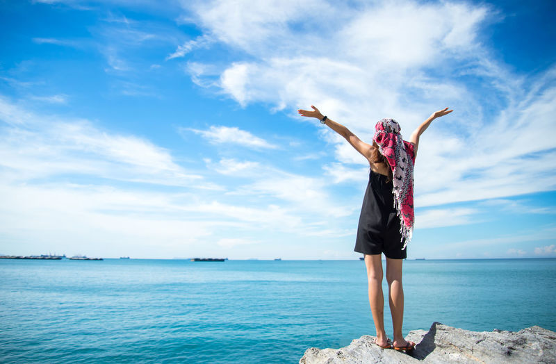 Full length of woman standing by sea against sky