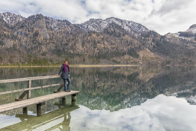 Full length of woman standing on pier over lake against mountains