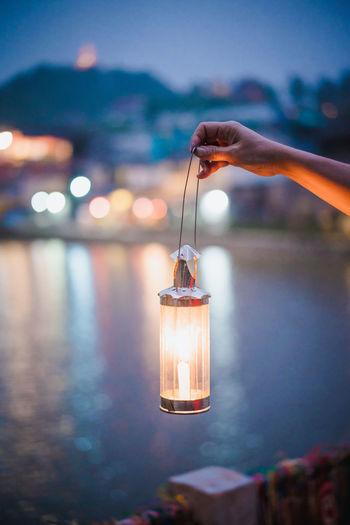 Cropped hand holding illuminated lantern against lake at dusk