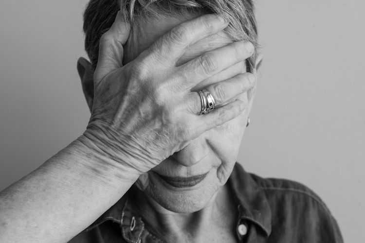 Woman covering face Headshot Human Hand Studio Shot Hand Portrait Front View Indoors  Emotion White Background Human Body Part Close-up One Person Adult Lifestyles Body Part Finger Human Face Obscured Face Woman