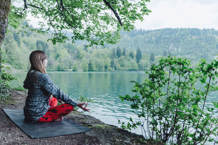 Side view of young woman meditating while sitting by lake against tree in park