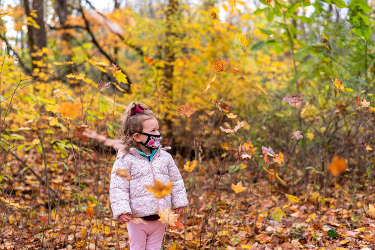 Girl standing on leaves during autumn