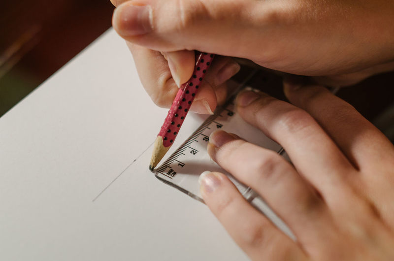 Close-up of hands making line with ruler on paper
