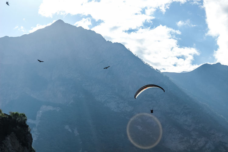 Person paragliding on mountain peak against sky