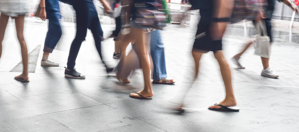Low section of people walking on floor