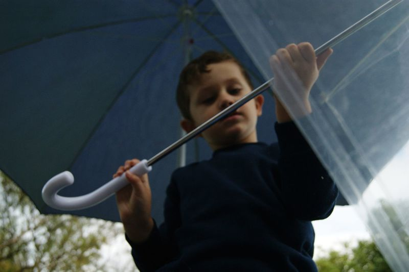 Low angle view of boy holding umbrella while standing outdoors