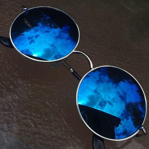 Close-up of sunglasses against blue sky