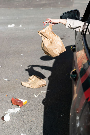 Cropped image of woman throwing garbage on street from car