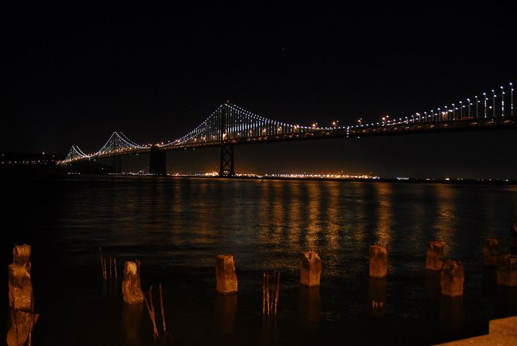 Illuminated oakland bay bridge over sea against sky