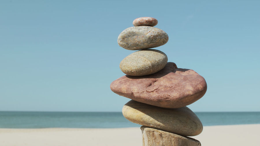 Close-up of stone stack on shore against clear sky